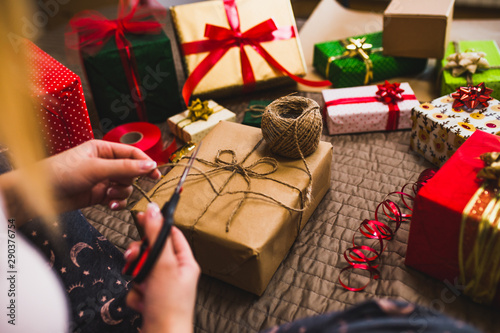 Gift wrapping. Woman packs holiday gifts at home.
