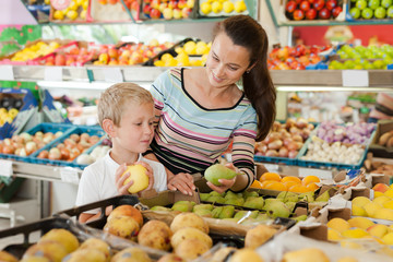 Boy with his mother choosing fruits