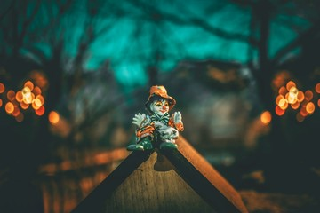 toy clown sits on wooden roof at his home in the forest. sad clown in the night. art detail close up photo.