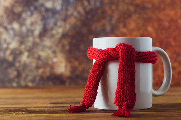 Spoed Foto op Canvas Thee Tea cup of tea with red warm knitted scarf. Autumn, fall background. Cold and illnes season.