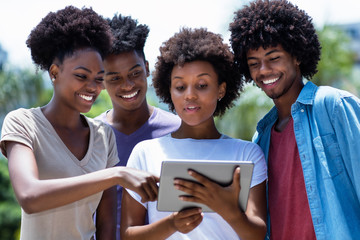 African american young adults reading news with digital tablet