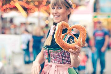 Fototapete - Junge Frau auf der Dult Oktoberfest hält Brezel