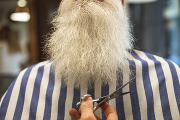 Barber man cutting senior's beard with a scissors