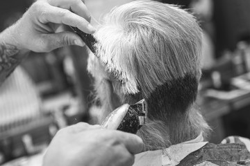 Hairdresser making stylish haircut for old man
