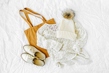 Wall Mural - Knitted white sweater with hat, shoes and tote bag. Autumn/winter fashion clothes collage on white background. Top view flat lay.