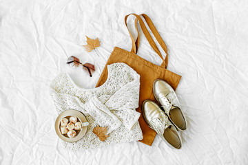 Wall Mural - Knitted white sweater with  tote bag and cocoa drink. Autumn/winter fashion clothes collage on white background. Top view flat lay.