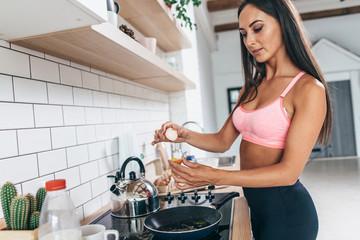 Girl in sport clothes preparing breakfast in the kitchen