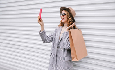 Stylish happy laughing woman taking selfie picture by smartphone with shopping bag in gray coat, round hat posing on city street over white wall background