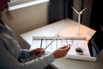 Businesswoman in suit sitting in office and holding windmill model. On desk are coffee, documentation and laptop. Sustainable concept. Wall mural