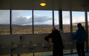 Tourists wash their hands in a bathroom overlooking snow-capped mountains at Thingvellir National Park