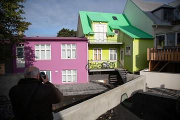 A man takes a picture of multi-coloured houses in Reykjavik