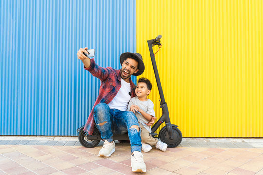 Young Father Taking a Selfie with his Son on an Electric Scooter.