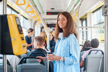 Stylish woman in blue shirt enjoying trip in the modern tram or bus, stands with cup of coffee in the public transport.