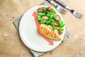 Intermittent fastin concept. One-third plate with healthy food and two-third plate is empty. Chicken fillet, arugula and tomatoes on a plate. Top view. Flat lay