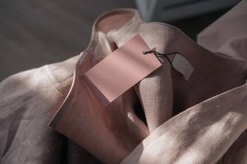 Pink linen dress with tag in white box. Branding mockup. Fashion blogging concept. Direct sunlight, lights and shadows photography