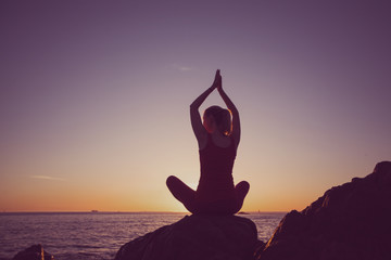 Silhouette of yoga woman on the seashore during sunset. Chrome photo.