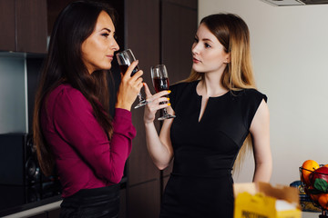 Two girlfriends in elegant clothes relaxing after shopping, drinking wine, laughing and gossiping in the kitchen