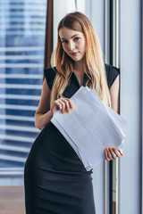 Portrait of pretty smiling young woman holding papers standing at window with cityscape view