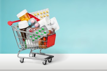 Shopping Cart with pills isolated on  background.