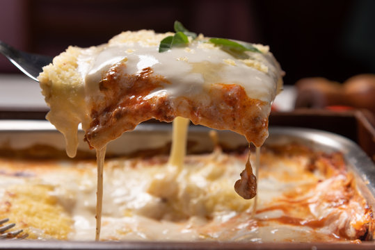 Delicious lasagna made with minced beef bolognese sauce and bechamel sauce topped with basil leaves, soft light