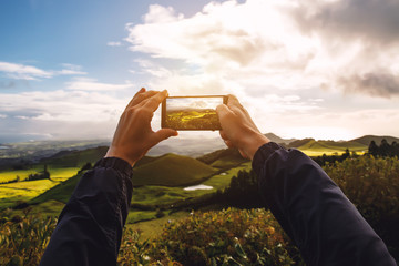 Man takes a photo of a beautiful green meadow on his smartphone