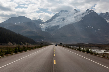 Wall Mural - Scenic road in the Canadian Rockies during a vibrant sunny and cloudy summer morning. Taken in Icefields Parkway, Jasper National Park, Alberta, Canada.