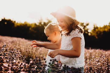 Lovely little girl laughing while running in a field of flowers with her brother. Small kid playing with his sister outdoor against sunset.