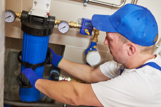 Plumber work. Installing water filter into system