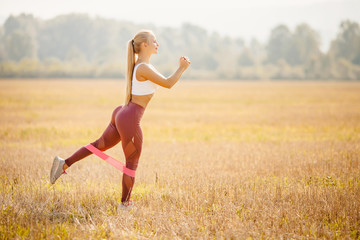 Fitness stretching rubber bands beautiful girl athlete blonde performs exercises outdoors in park