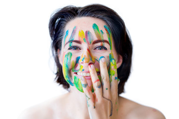 Young cheerful soiled in paint girl having fun. Smiling Woman with bright makeup isolated on White background. artistic colorful portrait of a young beautiful model with face covered with paint