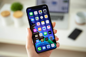 Woman hand holding iPhone X with home screen IOS 13