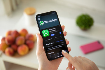 Woman holding iPhone X with social networking service WhatsApp