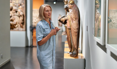 Mature woman visitor in the historical museum looking at pictures