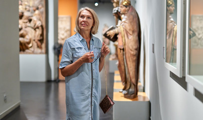 woman visitor looking at exhibition in museum of ancient sculpture.