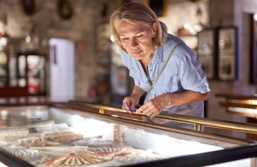 Woman visitor in the historical museum looking at art object.