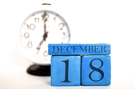 december 18th. Day 18 of month, handmade wood calendar and alarm clock on  blue color. winter month, day of the year concept