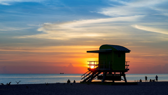Ocean beach sunrise with lifeguard tower and colorful cloud and blue sky, Miami Beach, Florida.