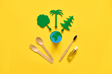 Less waste eco freindly flat lay. Green trees, Earth, wooden cutlery and toothbrush. no plastic