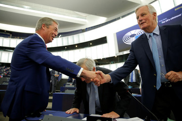 Brexit Party leader Nigel Farage shakes hands with European Union's chief Brexit negotiator Michel Barnier before a debate on Brexit at the European Parliament in Strasbourg