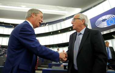 European Commission President Jean-Claude Juncker shakes hands with Brexit Party leader Nigel Farage before a debate on Brexit at the European Parliament in Strasbourg