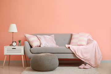 Cozy sofa with pouf and table near color wall in room