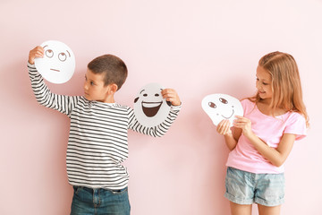 Little children with drawn emoticons on color background