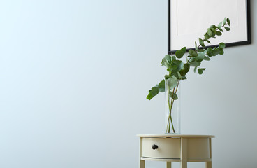 Table with eucalyptus branches in vase near light wall