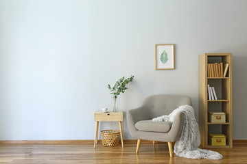 Stylish interior of room with armchair and eucalyptus branches in vase on table