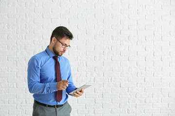 Portrait of businessman with tablet computer against white brick wall