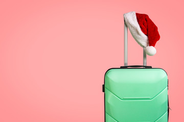 Plastic suitcase and Santa Claus hat on red background. Concept of travel to visit friends and relatives on Christmas holidays. Merry Christmas and Happy New Year. Christmas trip