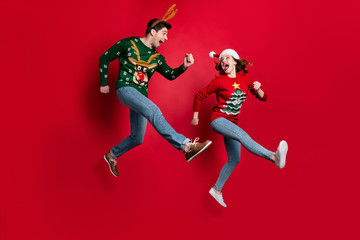 Full size photo of excited jumping couple run fast for x-mas discounts shopping wear ugly ornament jumpers isolated red color background