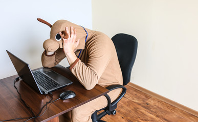 Office worker in cosplay costume of a cow. Guy in the funny animal pyjamas sleepwear near the laptop. Parody on desperate manager. Occupational burnout.