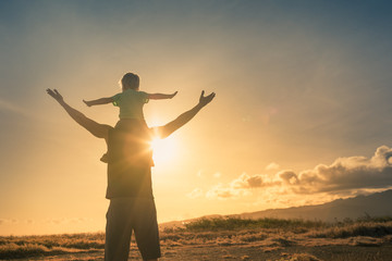 Father son having fun outdoors at sunset pretending to fly. Family adventure and freedom concept.