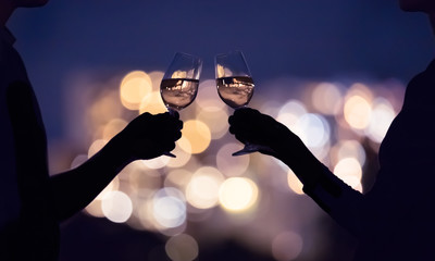 Couple drinking wine together against a city lights view. People celebrating together.